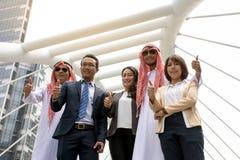 Asiatisk tumme för affärslagvisning upp för bra arbete med stadsbakgrund arkivbild