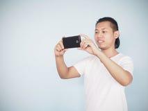 Asiatisk ung för t-skjorta för hipstermankläder vit mobiltelefon bruk till t Fotografering för Bildbyråer