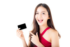 Asiatisk ung kvinna med den röda klänningen som rymmer en kreditkort och le Royaltyfri Foto