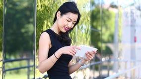 Asiatisk ung kvinna med minnestavlan lager videofilmer