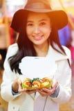 Asiatisk ung kvinna som äter gatamat i Hong Kong royaltyfri foto
