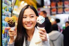 Asiatisk ung kvinna som äter gatamat i Hong Kong fotografering för bildbyråer