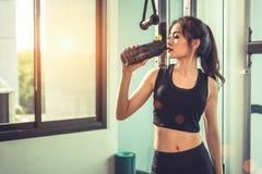 Asiatisk ung kvinna som dricker proteinskakan eller vatten efter övning royaltyfri fotografi