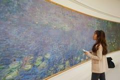 Asiatisk ung kvinna som ser runt om Louvremuseet och uppskattar skönheten av ett konstverk royaltyfria bilder