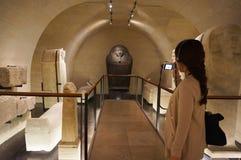 Asiatisk ung kvinna som ser runt om Louvremuseet och uppskattar skönheten av ett konstverk arkivbilder