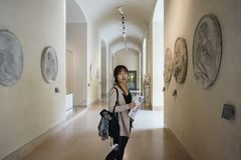 Asiatisk ung kvinna som ser runt om Louvremuseet och uppskattar skönheten av ett konstverk arkivfoto