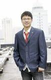 Asiatisk ung man i dräkt med tien Arkivfoto