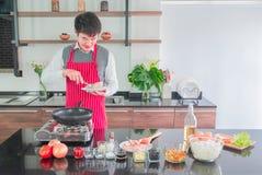 Asiatisk ung man i rött förkläde, med att le Laga mat för mat royaltyfri fotografi