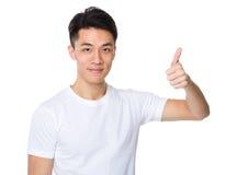 Asiatisk ung man med tummen upp Fotografering för Bildbyråer