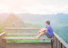 Asiatisk ung man som sitter på det främst av balkongen han tänker något arkivfoton
