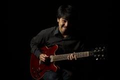 Asiatisk ung musiker som spelar gitarren Royaltyfria Foton