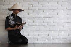 Asiatisk ung novis på en vit tegelstenvägg arkivbild