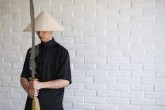 Asiatisk ung novis på en vit tegelstenvägg royaltyfri foto