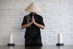 Asiatisk ung novis på en vit tegelstenvägg arkivbilder