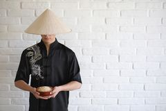 Asiatisk ung novis på en vit tegelstenvägg arkivfoto