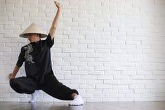Asiatisk ung novis på en vit tegelstenvägg arkivfoton
