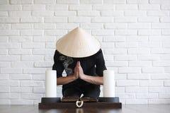 Asiatisk ung novis på en vit tegelstenvägg royaltyfria bilder