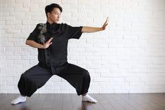 Asiatisk ung novis på en vit tegelstenvägg royaltyfri fotografi