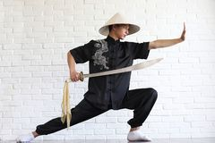 Asiatisk ung novis på en vit tegelstenvägg royaltyfria foton