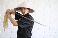 Asiatisk ung novis på en vit tegelstenvägg fotografering för bildbyråer