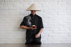 Asiatisk ung novis på en vit tegelstenvägg royaltyfri bild