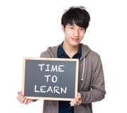 Asiatisk ung student med svart tavla som visar uttrycken av tid Fotografering för Bildbyråer