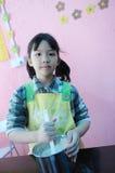 Asiatisk unge som gör kakor Arkivbild