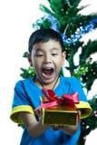 Asiatisk unge som upphetsar för att få en julgåva Arkivbild
