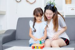 Asiatisk ungeflicka och moder som spelar leksakkvarteret; samman med gladlynt och lyckligt Arkivbild