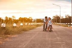 Asiatisk ungeflicka som har gyckel som rider cykeln med fadern Arkivfoton