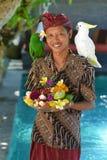 Asiatisk uppassare med ett magasin av tropiska frukter Arkivfoto