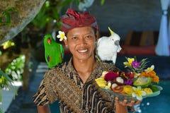Asiatisk uppassare med ett magasin av tropiska frukter Arkivbilder