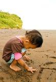 asiatisk writing för litet barn för strandflickasand Arkivfoton