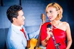 Asiatisk yrkesmässig musikbandinspelningsång i studio Royaltyfri Bild