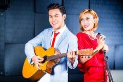 Asiatisk yrkesmässig musikbandinspelningsång i studio royaltyfri foto