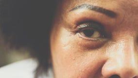 Asiatiska äldre kvinnor visar henne ögon och ögonbryntatueringen arkivbild