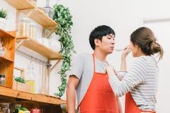 Asiatiska älskvärda par lagar mat tillsammans hemmastatt kök som smakar mat som förbereder mål Flickamatningssoppa till pojkvänne royaltyfri bild