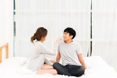 Asiatiska älskvärda par som tillsammans flörtar på säng i det vita sovrummet Flickvän och pojkvän som retar sig Royaltyfri Fotografi