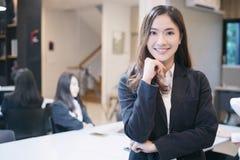 Asiatiska affärskvinnor och grupp som använder anteckningsboken för möte och bu arkivfoto