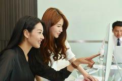 Asiatiska affärskvinnor som i regeringsställning använder datoren royaltyfri fotografi