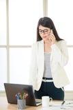 Asiatiska affärskvinnor som i regeringsställning arbetar och använder den smarta telefonen Royaltyfri Bild