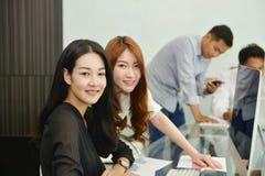 Asiatiska affärskvinnor som ler i mötesrum royaltyfria foton