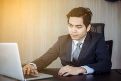 Asiatiska affärsmän som använder anteckningsboken och påfyllningen som är allvarliga om arbetet royaltyfria bilder