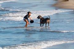 Asiatiska amerikanska kvinnalekar med hennes hund på hundstranden Royaltyfri Fotografi