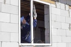 Asiatiska arbetare installerar f?nster till huset royaltyfri foto