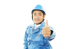 Asiatiska arbetarvisningtummar up tecknet Arkivfoton