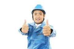 Asiatiska arbetarvisningtummar up tecknet Royaltyfri Foto