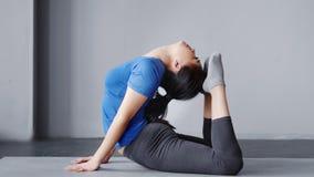 Asiatiska böjliga kvinnor som öva yoga i inomhus konditionkvinnlig för studio med perfekt sträckning
