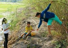 Asiatiska barn, bong dien dien, den Sesbania sesbanaen, den Mekong deltan Fotografering för Bildbyråer