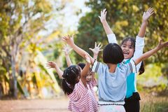 Asiatiska barn lyfter händer och att spela samman med gyckel royaltyfri bild